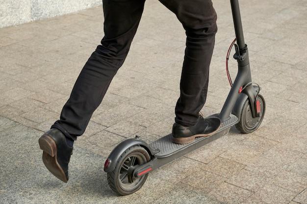 Mann, der auf elektrischem tretroller reitet