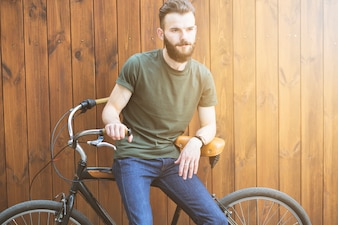 Mann, der auf Fahrrad gegen hölzernen Hintergrund sitzt