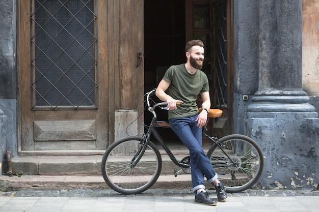 Mann, der auf fahrrad vor einer offenen tür sitzt