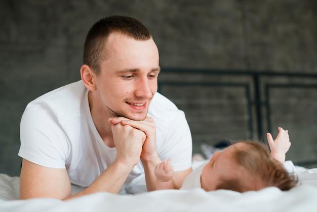 Mann, der auf faust beim lügen mit baby sich lehnt