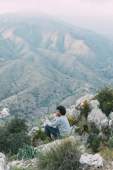Mann, der auf felsen in der natur sitzt