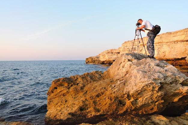 Mann, der auf felsen steht und foto mit stativ über schwarzem meer macht
