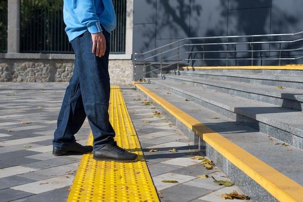 Mann, der auf gelben blöcken des taktilen pflasters für blindes handicap geht. brailleblöcke, taktile fliesen für sehbehinderte, tenji-blöcke