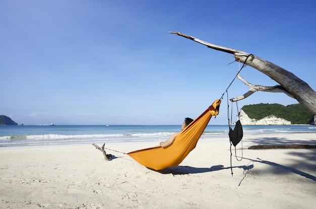Mann, der auf hängematte am tarimbang strand sich entspannt