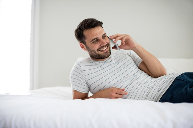 Mann, der auf handy im schlafzimmer zu hause spricht