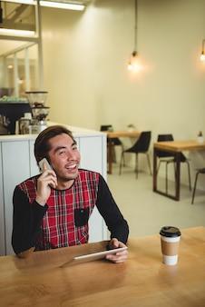 Mann, der auf handy spricht, während digitales tablett verwendet wird
