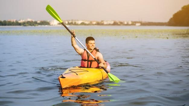 Mann, der auf idyllischem see unter verwendung des paddelns kayaking ist