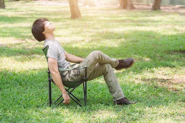 Mann, der auf kampierendem stuhl sich entspannt