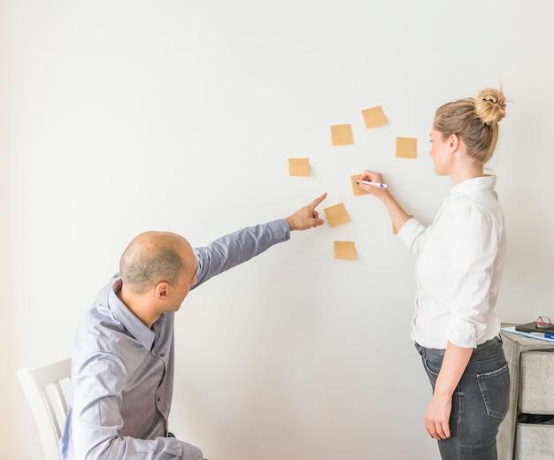 Mann, der auf klebende anmerkung während frauenschreiben auf klebriger anmerkung zeigt