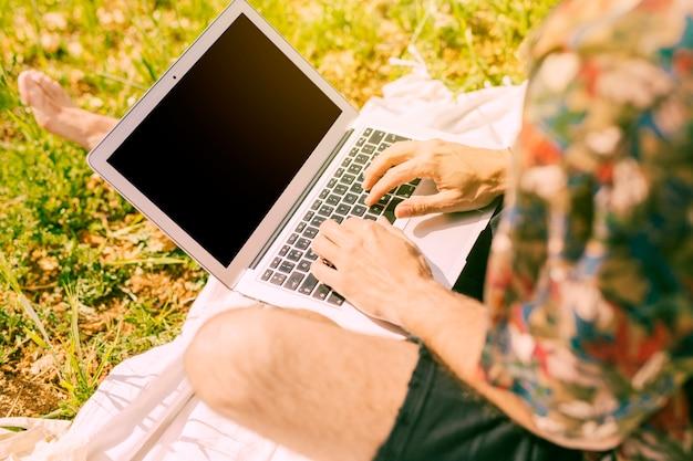 Mann, der auf laptop in der lichtung surft