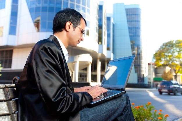 Mann, der auf laptop schreibt, der auf straße ist