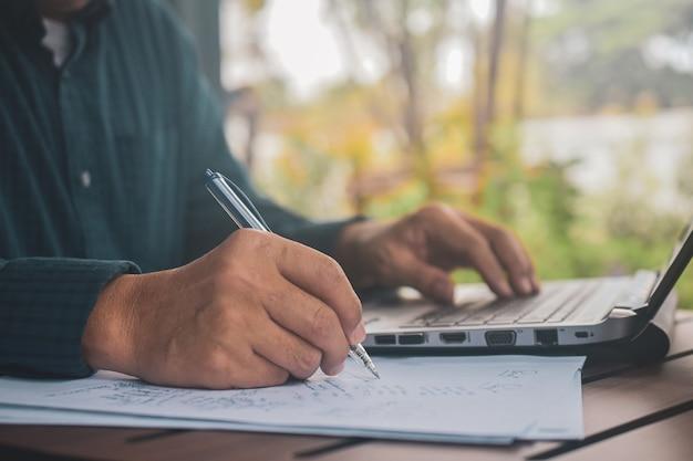 Mann, der auf laptop schreibt und auf papiere schreibt