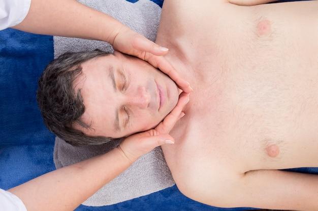 Mann, der auf massagetisch entspannt, der gesichtsmassage empfängt