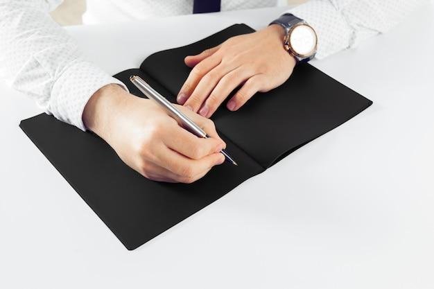 Mann, der auf notizbuch lernt und schreibt