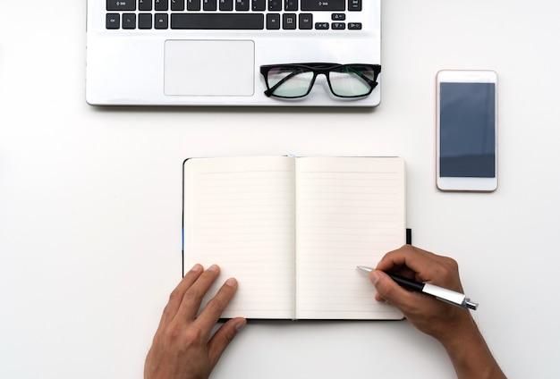 Mann, der auf notizbuch mit handy, computer und brille auf weißem tisch, draufsicht, kopienraum für text schreibt.