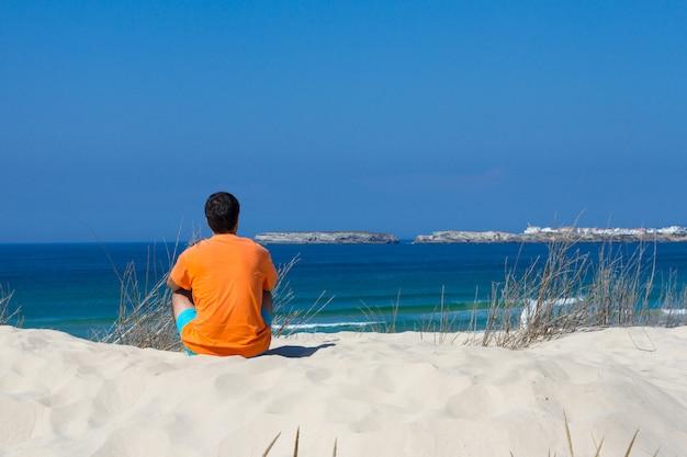 Mann, der auf sand nah an meer sitzt