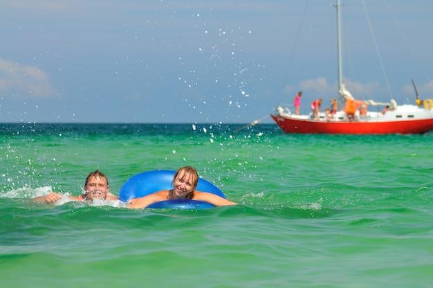 Mann, der auf schwimmkreis im meer reitet und am sonnigen sommertag lächelt. konzept für glück, urlaub und freiheit