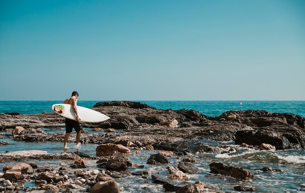 Mann, der auf seeufer mit surfbrett geht