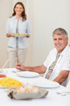 Mann, der auf seine frau wartet, um salat zum tisch zu holen
