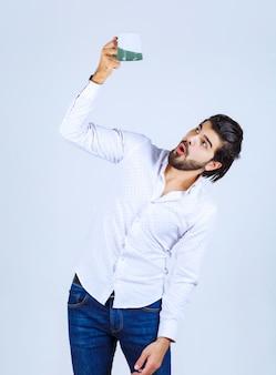Mann, der auf seine kaffeetasse schaut und verwirrtes gesicht zeigt
