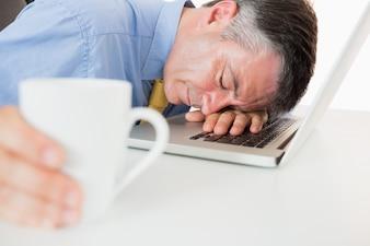 Mann, der auf seinem Laptop beim Halten des Kaffees schläft