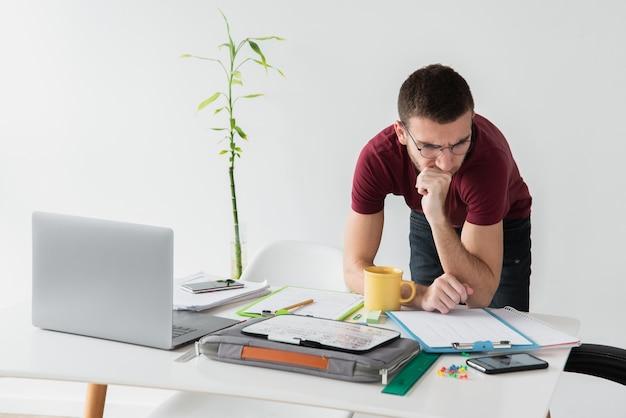 Mann, der auf seinem schreibtisch sich lehnt und fokussiert wird