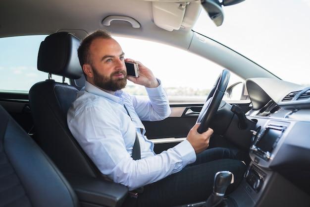Mann, der auf smartphone beim fahren des autos spricht