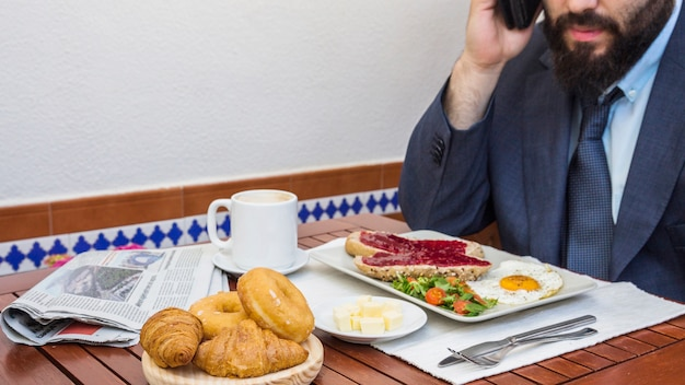 Mann, der auf smartphone mit lebensmittel auf tabelle spricht