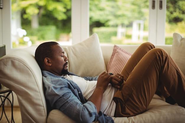 Mann, der auf sofa liegt und seine smartwatch benutzt