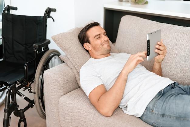 Mann, der auf sofa mit tablet nahe rollstuhl sich entspannt.