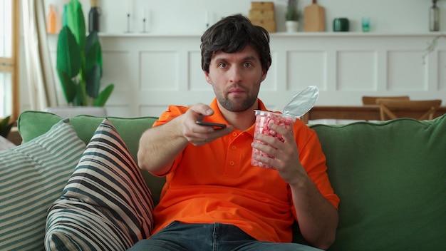Mann, der auf sofa sitzt, popcorn isst, fernbedienung hält und kanäle wechselt