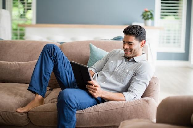 Mann, der auf sofa sitzt und digitales tablett im wohnzimmer verwendet