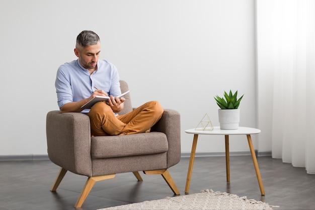 Mann, der auf stuhl sitzt und auf seine tagesordnung schreibt