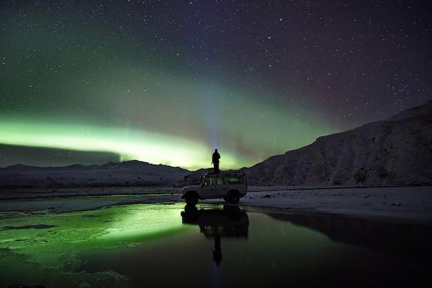 Mann, der auf suv steht und nordlichter beobachtet