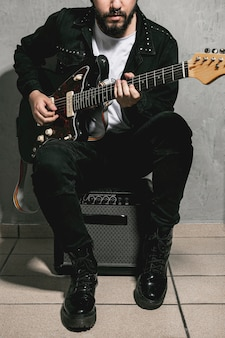 Mann, der auf verstärker sitzt und gitarre spielt