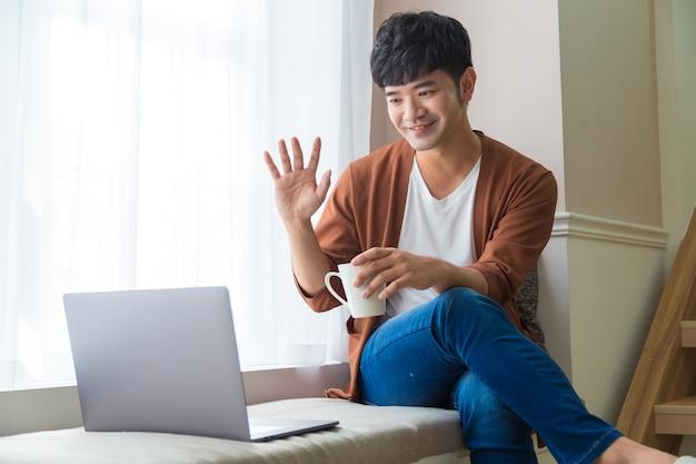 Mann, der auf videokonferenz online mit laptop spricht und nahe fenster zu hause sitzt. studieren sie auf online-fernkurs. sprechen sie per videoanruf mit einem freund oder verwandten.