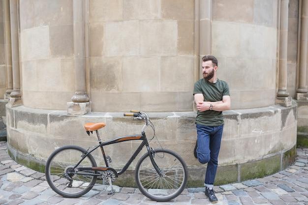 Mann, der auf wand nahe bei seinem fahrrad sich lehnt