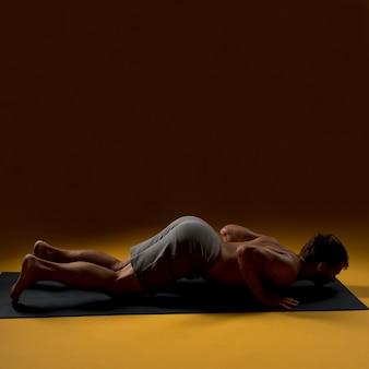 Mann, der auf yogamatte niederlegt