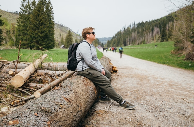 Mann, der auf zweig sitzt, der auf die schöne natur wilde natur schaut. konzept für reisen und aktives leben. draußen