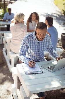 Mann, der auf zwischenablage schreibt, während laptop verwendet wird