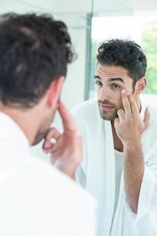 Mann, der augen im badezimmerspiegel überprüft