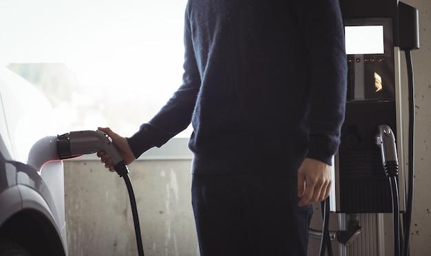 Mann, der auto an der ladestation des elektrofahrzeugs auflädt