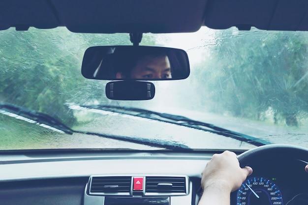 Mann, der auto in starken regenfällen fährt