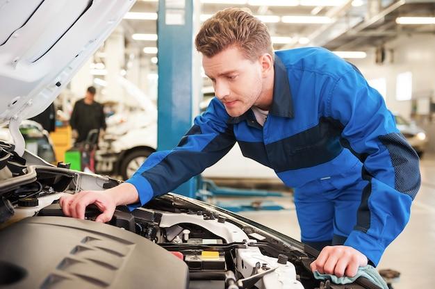 Mann, der auto repariert konzentrierter junger mann in uniform, der auto repariert, während er in der werkstatt steht