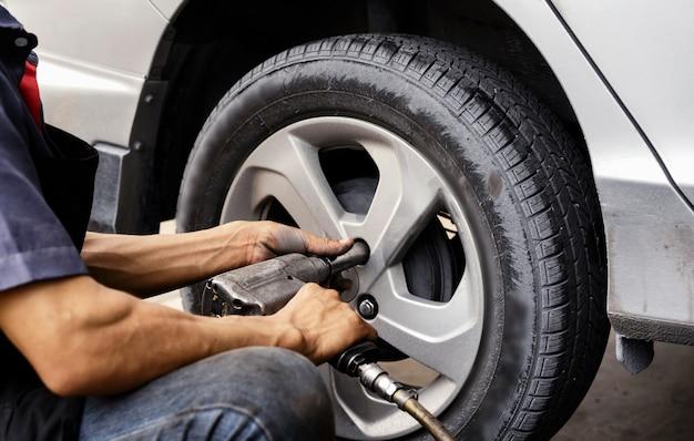 Mann, der automechaniker verwendet blockieren sie das windrad. so überprüfen sie ihre reifen und bremsen für das auto. kfz-mechaniker vorbereitung für die arbeit.