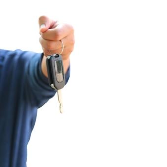 Mann, der autoschlüssel auf einem weißen hintergrund hält.