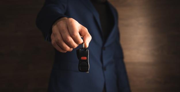 Mann, der autoschlüssel auf hölzernem hintergrund hält