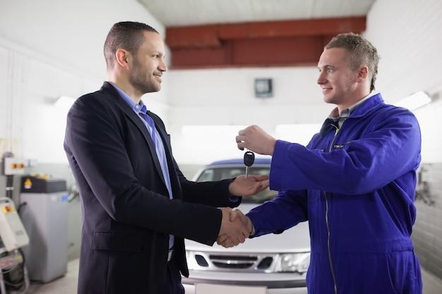 Mann, der autoschlüssel beim rütteln der hand zu einem mechaniker empfängt