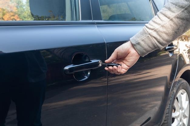 Mann, der autoschlüssel in das schwarze türschloss einführt, um zu öffnen
