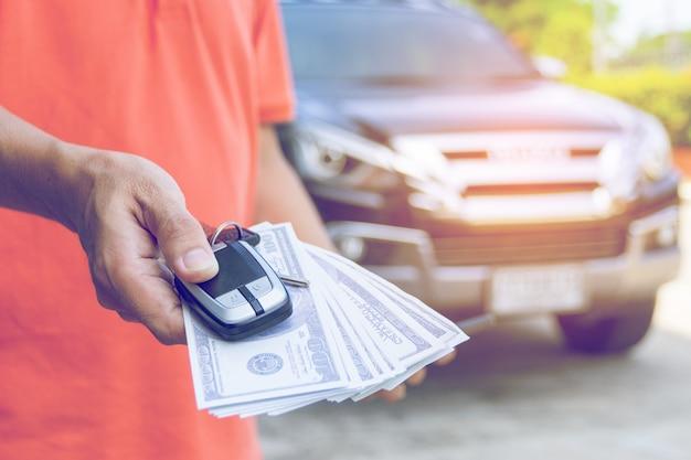 Mann, der autoschlüssel und -dollar mit auto hält